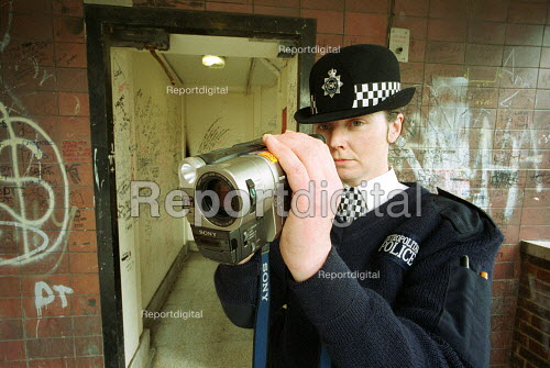 Police Officer using a Video camera on a deprived estate to film gangs of youths who are involved in race hate & anti social behaviour. London - Duncan Phillips - 2000-10-18