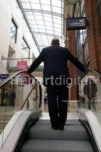 Report digital photojournalism - Man in suit on escalator in