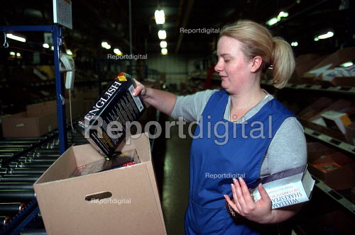Women worker packing books into cardboard box on a production line at OUP automated print distribution centre Corby - John Harris - 1999-12-16