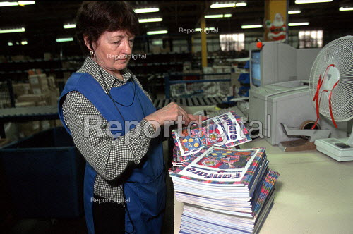 Older women worker packing magazines on a production line at OUP automated print distribution centre Corby - John Harris - 1999-12-16