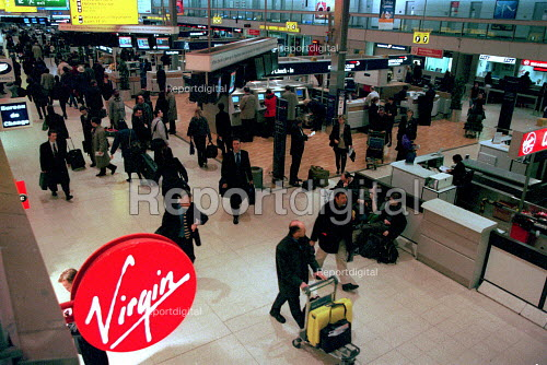Passengers carrying luggage at check in Terminal 3 Heathrow Airport. - John Harris - 2000-03-29