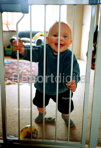 Baby boy at home in front room, 11 months of age with safety gate, football and a smile. - John Harris - 2000-04-20