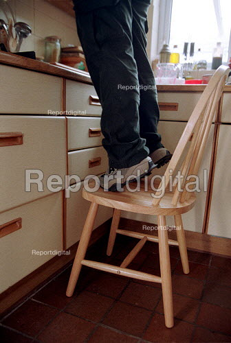 Safety in the home, women balancing on a chair in kitchen to reach shelf. - John Harris - 2000-05-04