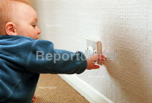 Safety in the home, baby boy playing with electricity socket cover. - John Harris - 2000-05-04