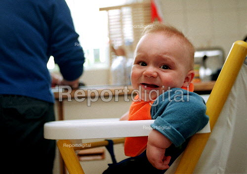 Baby boy at 11 months crying as his mother washes up in the kitchen at home. - John Harris - 2000-05-04
