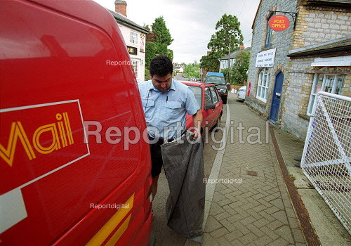 Postal worker collecting post from rural village post office. - John Harris - 2000-05-18