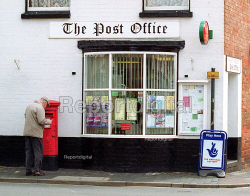 Elderly man posting a letter at a postbox outside a post office and corner shop. - John Harris - 2000-05-18