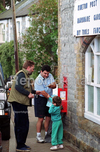 Child giving a letter to a postal worker collecting post from rural village postbox outside a post office. - John Harris - 2000-05-18