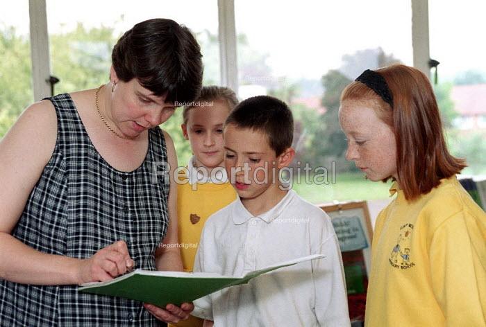 Teacher helping pupils in class at Primary School. - John Harris - 2000-06-09