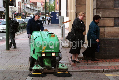 Street cleaner sweeping the pavement, as women go to work. Birmingham - John Harris - 2000-05-18