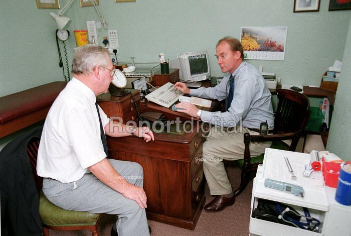 Doctor talking to elderly patient, GP surgery. - John Harris - 2000-06-29