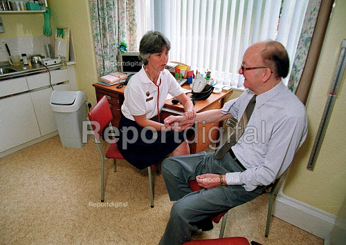 Nurse talking to elderly patient and taking his pulse, GP surgery. - John Harris - 2000-06-29
