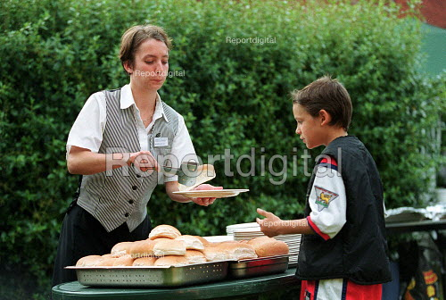 Part time women catering worker, a student, serving food. - John Harris - 2000-07-07