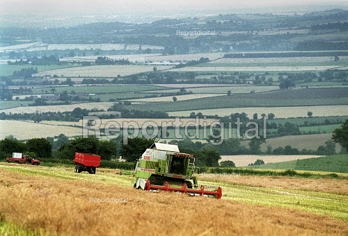 Combine Harvester harvesting wheat on a farm in Warwickshire. - John Harris - 2000-07-28