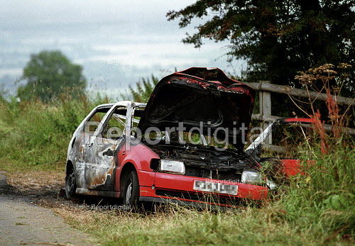 Stolen car burnt out and a dumped by joy riders in a country lane. - John Harris - 2000-07-28