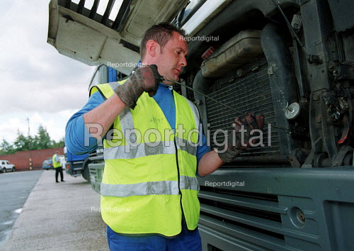 Driver checking oil level on a HGV vehicle at a chilled food products distribution centre, Express Chilled Distribution. - John Harris - 2000-08-02