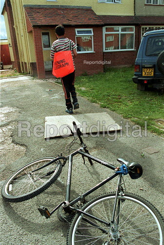 Paperboy on his delivery round with his bag of newspapers and bicycle. - John Harris - 2000-08-16