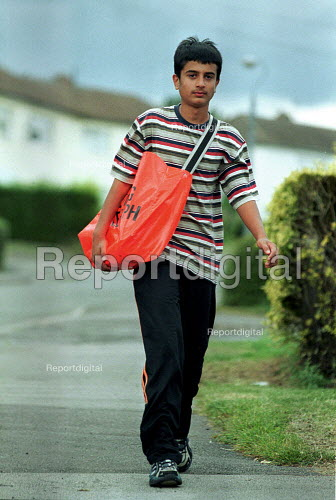Paperboy on his delivery round with his bag of newspapers. - John Harris - 2000-08-16