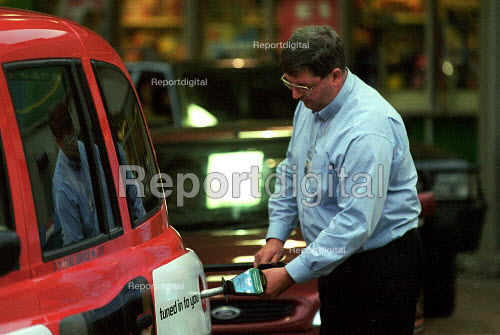 Taxi driver filling his vehicle with diesel on a petrol station forecourt having waited in a queue with other motorists for some time during fuel shortage crisis due to blockades in protest at high fuel prices and fuel tax. - John Harris - 2000-09-13