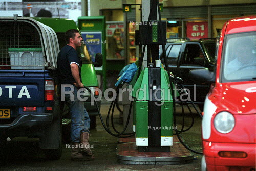 Driver filling his vehicle with diesel on a petrol station forecourt having waited in a queue with other motorists for some time during fuel shortage crisis due to blockades in protest at high fuel prices and fuel tax. - John Harris - 2000-09-13