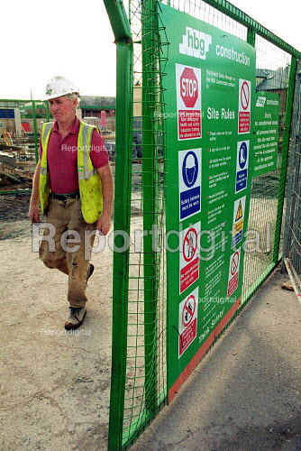 Construction worker walking past a building site Health and safety notice showing site rules. Construction site Worcester. - John Harris - 2000-10-04