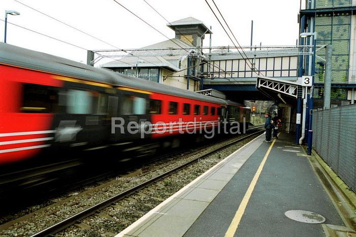 Passenger train speeding through a local railway station on the electrified east coast line. - John Harris - 2000-10-07