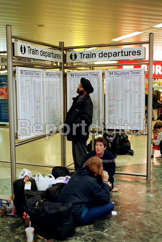 Passengers on Euston railway station concourse looking at timetables and waiting. - John Harris - 2000-10-20