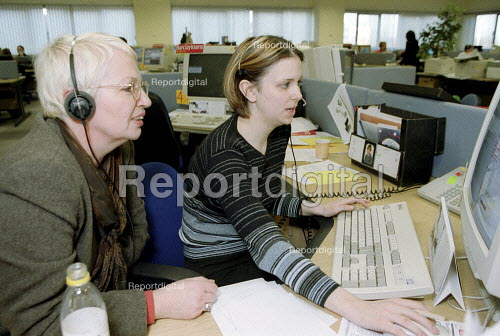 Young women worker training older worker in following screen prompts and software at Barclaycall banking call centre Coventry. - John Harris - 2001-01-16