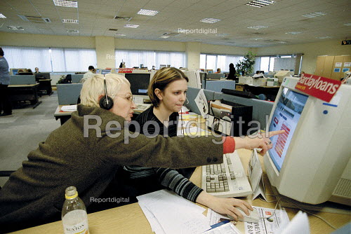 Older women worker training younger worker in following screen prompts and software at Barclaycall banking call centre Coventry. - John Harris - 2001-01-16