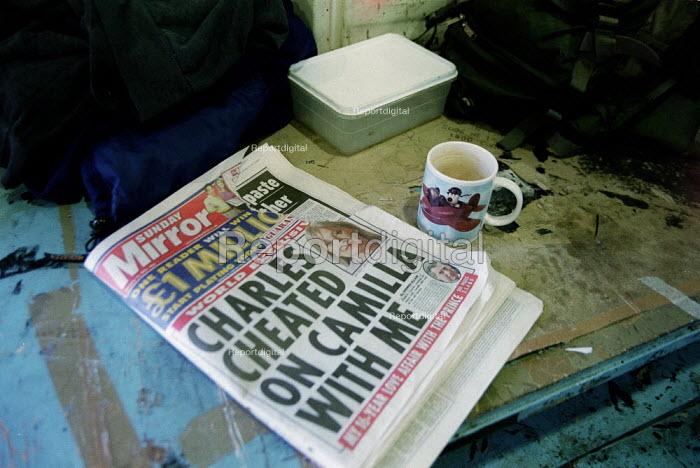 Mirror newspaper, tea mug and sandwich box on work bench in a factory. - John Harris - 2001-01-16