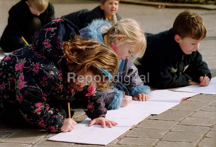 Young schoolchildren sketch in a park. - John Harris - 2001-03-06