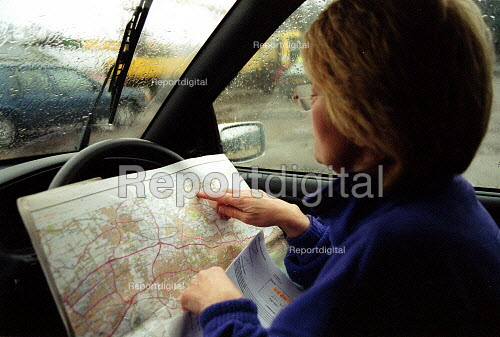Maff Animal Health Officer in her car, looking on an Ordnance Survey Map to locate a farm to carry out an inspection, checking for symptoms of foot and mouth disease in an at risk area. - John Harris - 2001-03-28