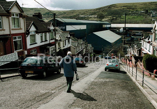 Retired steelworker walking down street of houses above Corus Ebbw Vale steelworks, South Wales valleys. - John Harris - 2001-04-04