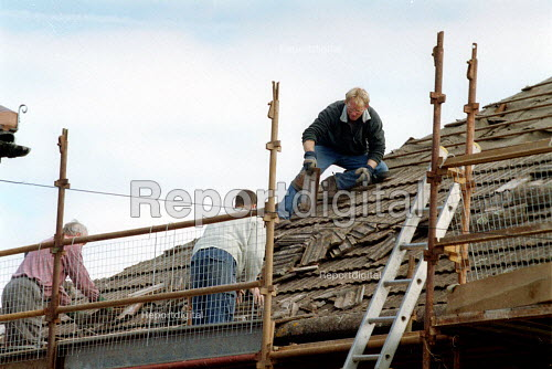 Roofers replacing roof tiles on a housing estate. - John Harris - 2001-04-11