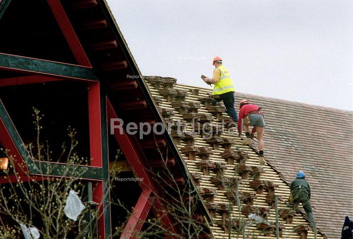 Roofers laying roof tiles on a new Tesco supermarket development. - John Harris - 2001-04-11