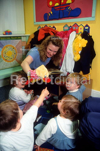 Nursery assistant reading toddlers a story featuring a duck which goes quack. - John Harris - 2001-04-10