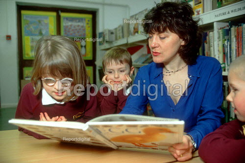 Parent helping pupils to read in school library. - John Harris - 2001-04-06