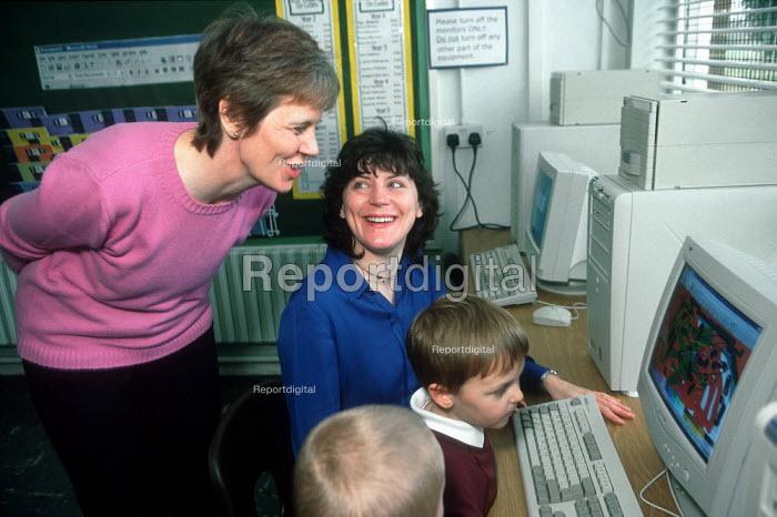 Teacher with parent helping pupils with computers in school. - John Harris - 2001-04-06