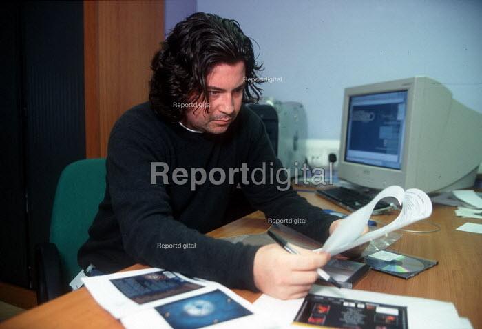 Designer working on a computer at printing factory. - John Harris - 2001-04-04