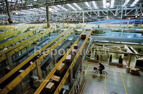 Post Officer worker on his bike, parcels on automated line Post Office Parcel Force Royal Mail Coventry Hub distribution centre. - John Harris - 2001-05-10