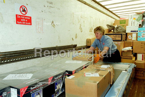 Woman Post Office worker unloading parcels from a lorry. Post Office Parcel Force Royal Mail Coventry Hub distribution. - John Harris - 2001-05-10