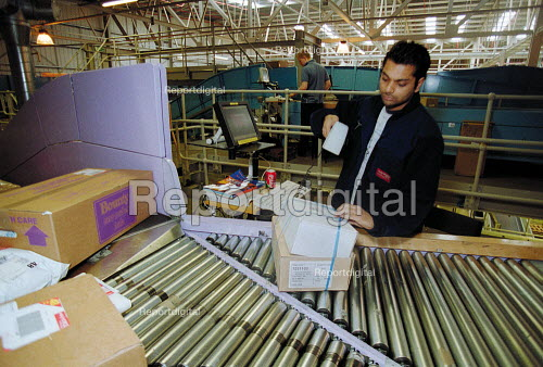 Post Office worker scanning barcoded packages. Post Office Parcel Force Royal Mail Coventry Hub distribution. - John Harris - 2001-05-10