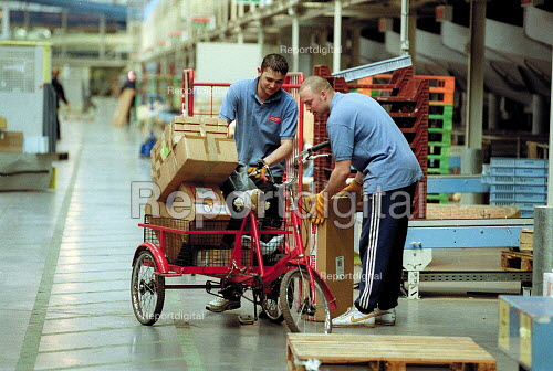 Post Office workers unloading parcels from a bicycle used internally with the sorting office which is a quarter of a mile long. Post Office Parcel Force Royal Mail Coventry Hub distribution. - John Harris - 2001-05-10
