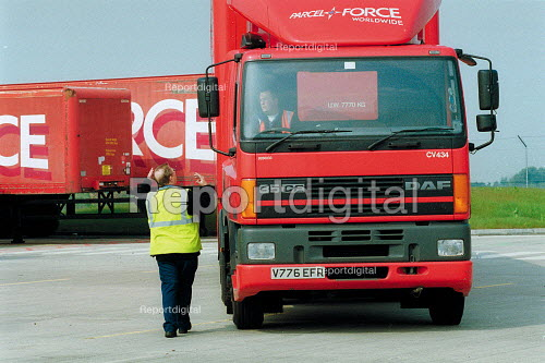 HGV driving instructor and truck driver with a 38 ton lorry, having just passed his HGV license driving test. Parcel Force Royal Mail Coventry Hub. - John Harris - 2001-05-10