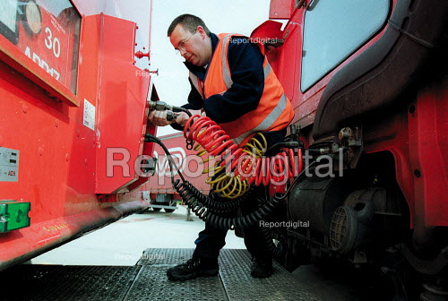 Truck driver fitting hydraulic hoses to trailer of a 38 ton lorry, having just passed his HGV license driving test. Parcel Force Royal Mail Coventry Hub. - John Harris - 2001-05-10