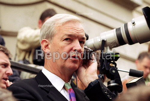 Jon Snow channel 4 TV news presenter on his mobile phone whilst waiting opposite No 10 Downing Street the morning after the General Election Campaign. - John Harris - 2001-06-08