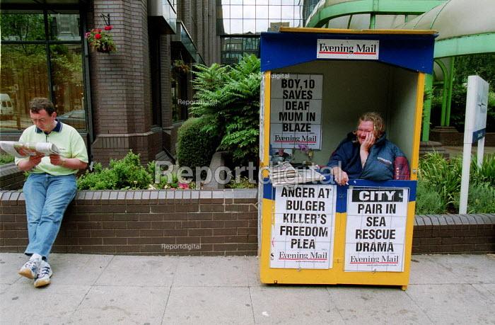 Man reading a newspaper in the street by a Evening Mail newspaper seller. Birmingham. - John Harris - 2001-06-18