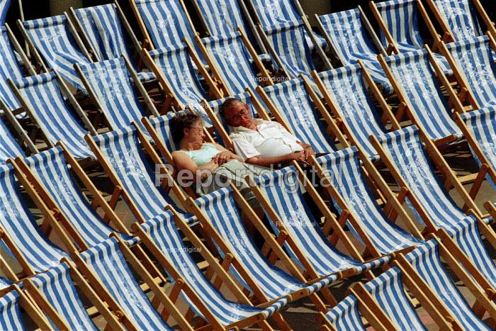 Elderly couple asleep in deckchairs on the seafront, Eastbourne. - John Harris - 2001-06-14