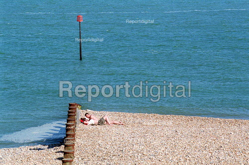 Couple relaxing and sunbathing on the pebble beach, Eastbourne. - John Harris - 2001-06-14