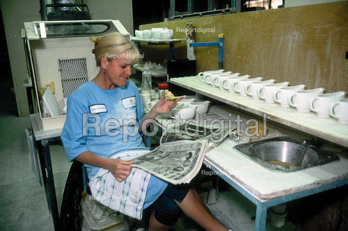 Women worker reading a sun newspaper and eating whilst taking lunch break on a production line at Churchill ceramics factory in the Potteries, Stoke on Trent. - John Harris - 2001-06-14